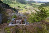 foto of derelict  - Looking down the welsh valley of Cwm Penmachno derelict incline drum house disused slate quarry in foreground - JPG