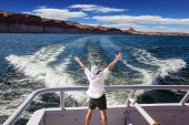 stock photo of fascinator  - Man in  white shirt on the stern boat fascinated by nature - JPG