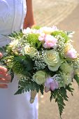 picture of ivory  - Bride holding her bridal bouquet ivory roses and pink fresia - JPG