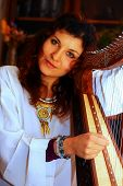 foto of celtic  - Young woman playing celtic harp in a white angelic historical costume - JPG