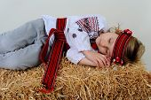 foto of haystack  - Ukrainian girl in national dress and jeans sleeps on a haystack - JPG