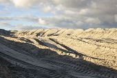 picture of caterpillar  - Piles of sand with caterpillar traces against the cloudy sky - JPG