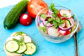 image of chinese parsley  - Spring salad with radishes cucumber Chinese cabbage and red onion closeup in glass bowl on a white wooden background - JPG