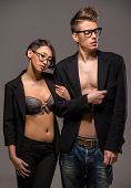 stock photo of tuxedo  - Young fashionable couple in glasses and tuxedos posing in the studio on dark background - JPG