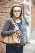 stock photo of she-male  - Teenage Girl Feeling Intimidated As She Walks Home - JPG