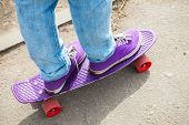 pic of snickers  - Riding skateboarder feet in a blue jeans and purple gumshoes selective focus with shallow DOF - JPG