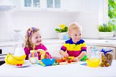 image of healthy eating girl  - Little girl and boy preparing breakfast in kitchen - JPG