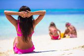 picture of sunny beach  - Young mother and her adorable daughters having fun at exotic beach on sunny day - JPG
