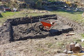 picture of spade  - Digging in the ground to preapare the foundation to a small house using a wheel barrow and spades - JPG