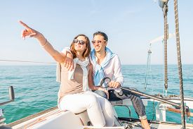 stock photo of boat  - Beautiful couple of lovers sailing on a boat  - JPG