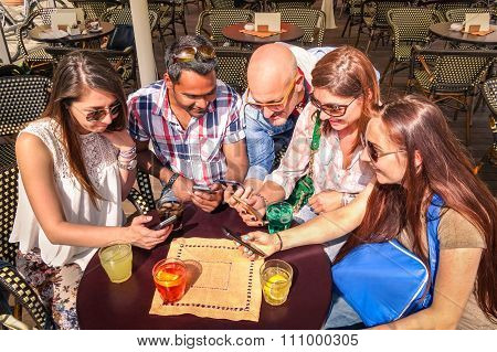 Group Of Multiracial Friends in Cafe Having Fun With Smartphone