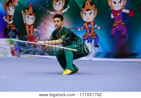 JAKARTA, INDONESIA - NOVEMBER 15, 2015: Melvin Tan of Australia performs the movements in the men's Gunshu (staff) event at the 13th World Wushu Championship 2015 held at Istora Senayan, Jakarta.