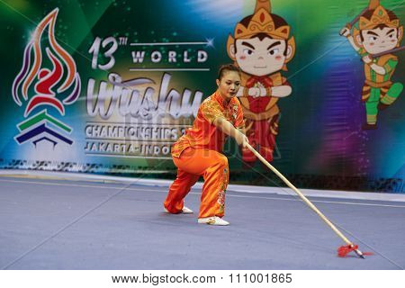 JAKARTA, INDONESIA - NOVEMBER 15, 2015: Eyin Poon of Malaysia performs the movements in the women's Qiangshu (spear) event at the 13th World Wushu Championship 2015 held in Istora Senayan, Jakarta.