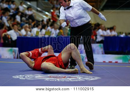 JAKARTA, INDONESIA - NOVEMBER 15, 2015: Bruce Tran of Canada (red) gets knocked down of YauhenSliaptsou of Belarus in the men's 65kg Sanda event at the 13th World Wushu Championship 2015.