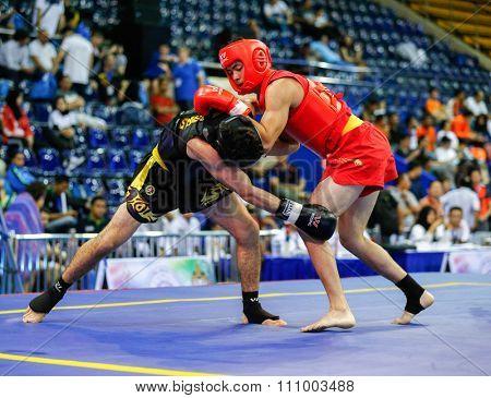 JAKARTA, INDONESIA - NOVEMBER 15, 2015: Reginald Sudarsana of Australia (red) fights Fardin Javanmard of Switzerland (black) in the men's 70kg Sanda event at the 13th World Wushu Championship 2015.