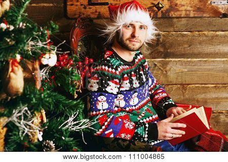 A Young Man In A Christmas Sweater Happily Looks Into The Frame