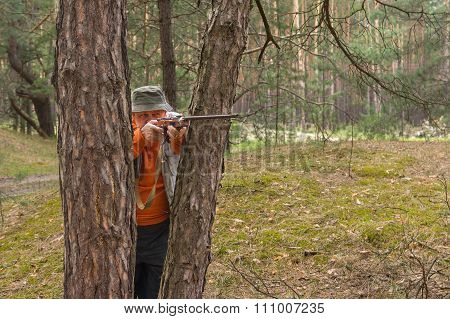 Senior hunter aim rifle standing between pine trees
