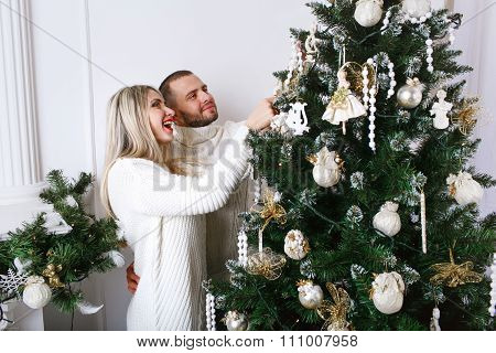 Young Beautiful Happy Couple Decorating Christmas Tree