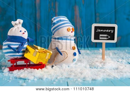 Word January written on direction sign and Snowman with red sled. Christmas, New year, winter decora