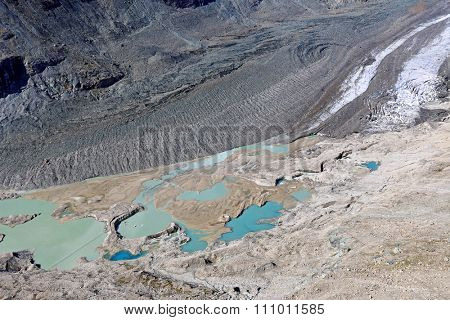 View of melted snow, moraine and crevasses at Pasterze Glacie, Grossglockner, Hohe Tauern National Park in Austria. It is the longest mountain glacier in Austria at approximately 8.4 km in length