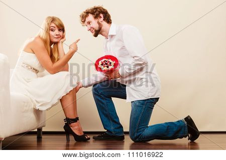 Man Giving Unhappy Woman Candy Bunch Flowers.