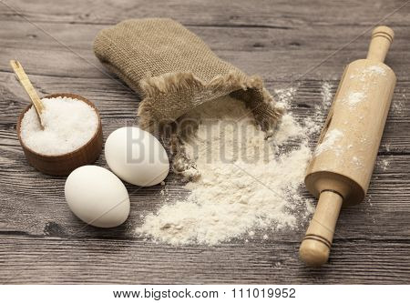 Wheat flour in a canvas bag, a large salt shaker wood, raw eggs, a wooden rolling pin: set for making homemade bread dough on a beautiful dark wooden background.