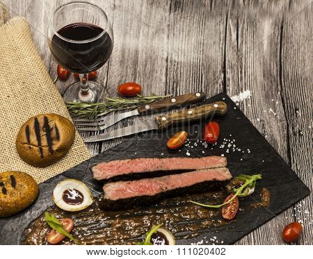 Ribeye steak from marble beef meat with vegetables and barbecue sauce. Served on a plate of black stone with fork and knife and wine