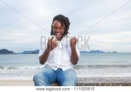 African American Guy With Dreadlocks And White Shirt Receiving Good News