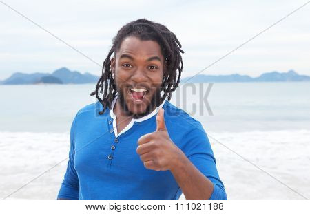 African American Guy With Dreadlocks At Beach Showing Thumb Up