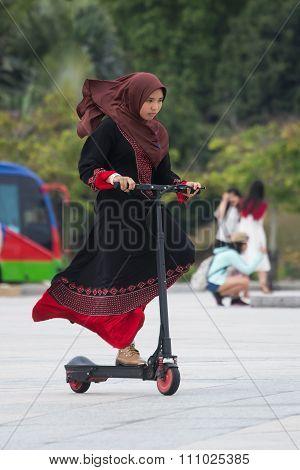 Putrajaya, Malaysia - Circa September 2015: Malaysian Girl In Traditional Dress And Hijab Is Riding