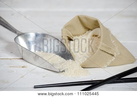 Rice In Small Hessian Bag On Wooden Table