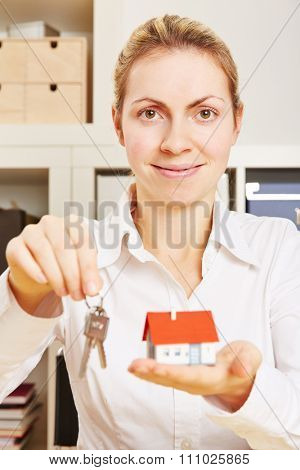 Female realtor with a small house and keys on a keychain in her hands