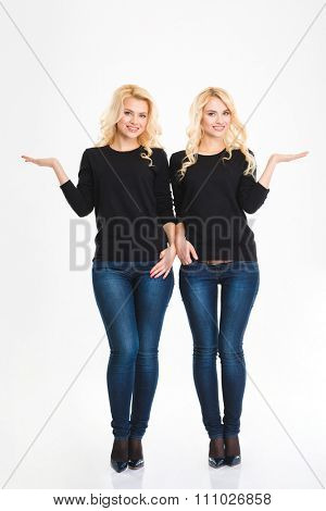 Full length portrait of a sisters twins holding copyspace on the palms isolated on a white background