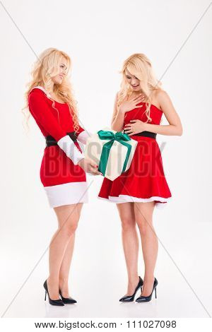 Happy excited sisters twins in red santa claus costumes giving and getting gifts over white background