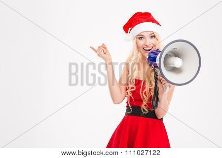 Beautiful cheerful young woman in santa claus costume and hat talking in speaker and pointing away over white background