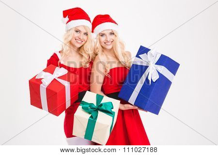 Two attractive happy sisters twins in santa claus costumes and hats holding presents over white background