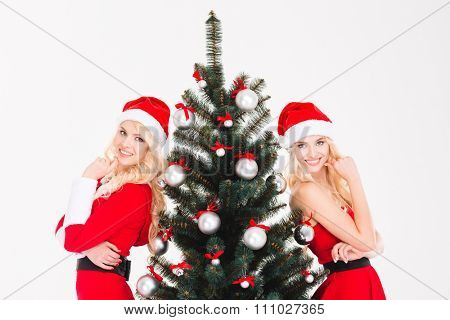 Attractive cheerful sisters twins in red santa claus clothes and hats posing near Christmas tree over white background