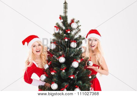 Happy excited sisters twins in red santa claus costumes and hats hiding behind the Christmas tree over white background