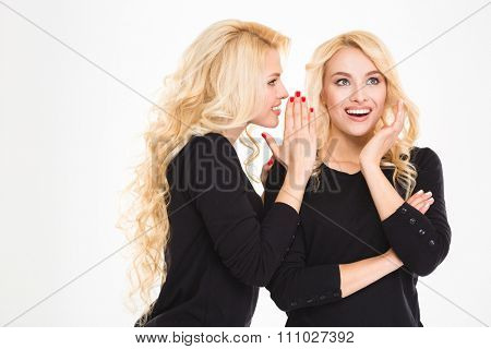 Portrait of a happy sisters twins gossiping isolated on a white background
