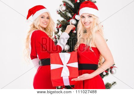 Two attractive blonde sisters twins in red santa claus costumes and hats holding present and decorating Christmas tree over white background