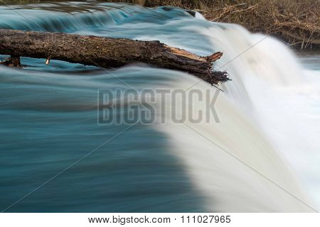 Log on top of waterfall resisting flow of river