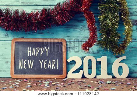 tinsel of different colors and a chalkboard with the text happy new year written in it and three-dimensional white numbers forming the number 2016, on a rustic wooden surface sprinkled with confetti