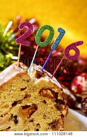 closeup of four glittering numbers of different colors forming the number 2016, as the new year, topping a fruitcake with some tinsel and ornaments in the background