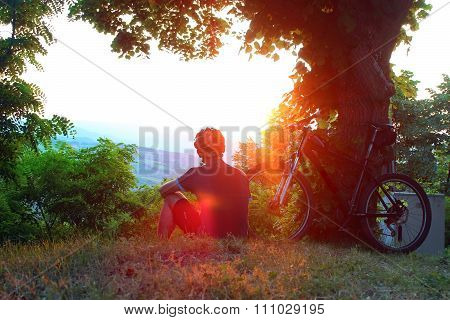 Cyclist relaxing on top of hill, watching the sunset