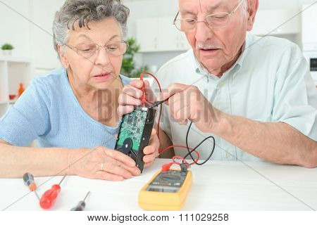 Elderly couple testing hard drive with multimeter