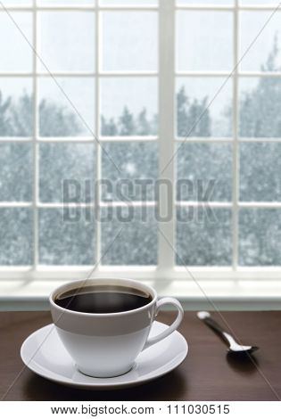 A cup of coffee and snowstorm view from the window on the background