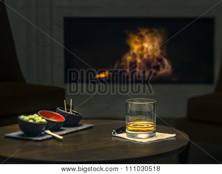 Glass of whiskey in front of the fireplace