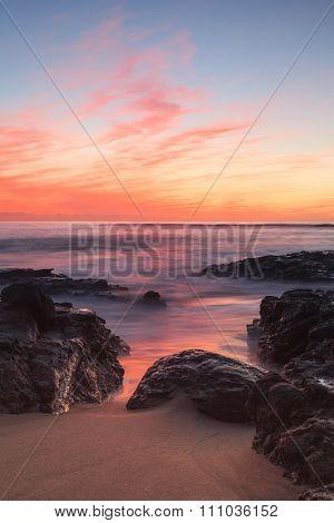 Long exposure of rocks and seaweed moss in waves