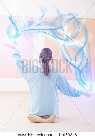 Beautiful woman doing qi gong tai chi exercise or reiki wearing professional, original Chinese clothes at gym