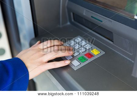 finance, technology, money and people concept - close up of hand entering pin code at cash machine